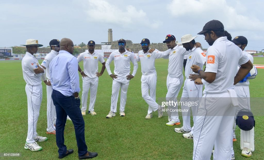Sri Lankan chief cricket selector Sanath Jayasuriya (L) chats with cricketers before the fourth day of the first Test match between Sri Lanka and India at Galle International Cricket Stadium in Galle on July 29, 2017. /