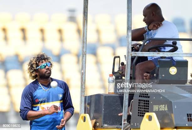Sri Lankan chief cricket selector Sanath Jayasuriya speaks with player Lasith Malinga during a practice session ahead of the third oneday...