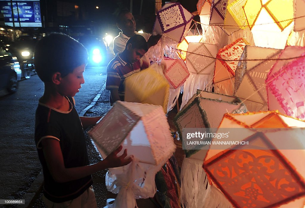 Sri Lankan child by a lantern at a temporary shop in Colombo on May 25, 2010, ahead of the key Buddhist festival of Wesak. Buddhists commemorates the birth of Buddha, his attaining enlightenment and his passing away on the full moon day of May which falls on May 27 this year. AFP PHOTO/Lakruwan WANNIARACHCHI