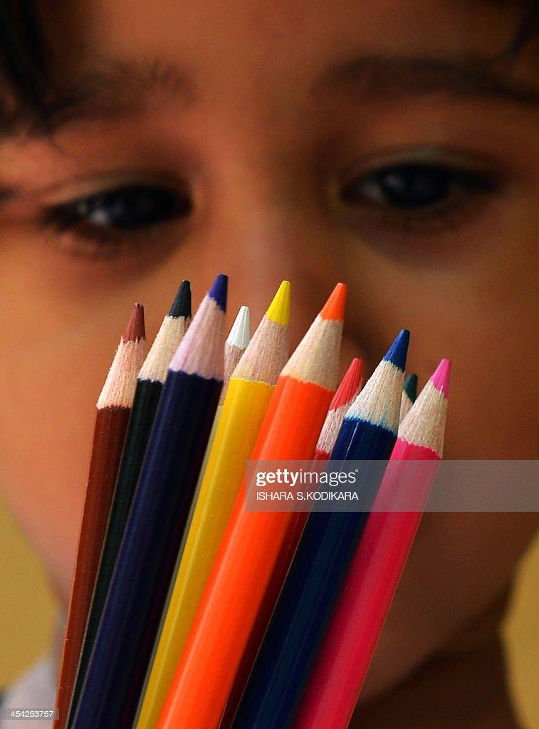 A Sri Lankan child holds up coloured pencils in Kelaniya on December 8, 2013. AFP PHOTO/ Ishara S