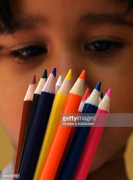 A Sri Lankan child holds up coloured pencils in Kelaniya on December 8 2013 AFP PHOTO/ Ishara SKODIKARA