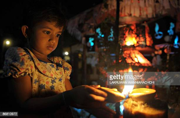 A Sri Lankan child lights a coconut oil lamp on Wesak day in Colombo on May 8 2009 Wesak the holiest day in the Buddhist calendar is commemorated to...