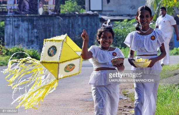 Sri Lankan children carry lanterns on their way to school on the eve of the Buddhist festival of Vesak on May 18 2008 in Colombo as the predominantly...