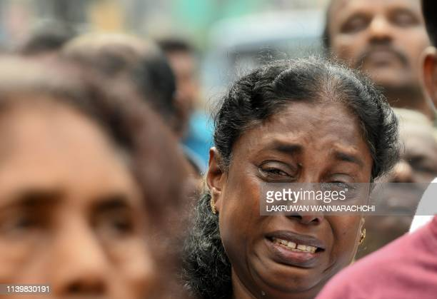 Sri Lankan Christian devotee cries as she prays at a barricade near St Anthony's Shrine in Colombo on April 28 a week after a series of bomb blasts...