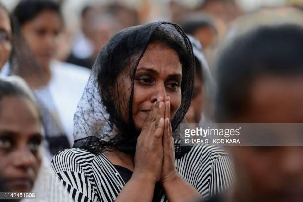 Sri Lankan Christian devotee cries as she prays during a mass outside St Sebastian's Church after it was partially opened for the first time since...