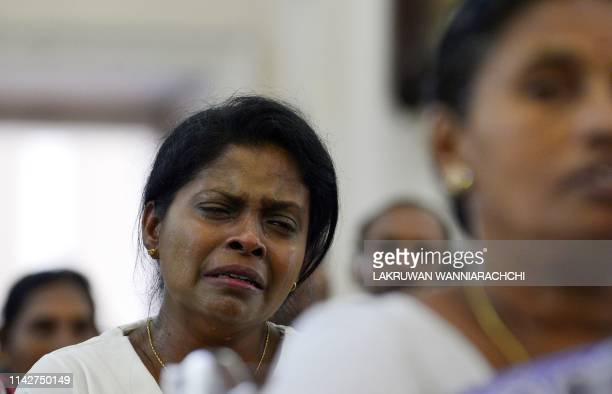 A Sri Lankan Christian devotee reacts as she prays at St Lucia's Cathedral during a holly mass held to bless the victims of Easter Sunday attacks in...