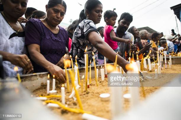 TOPSHOT Sri Lankan Christian devotees light candles as they pray at a barricade near St Anthony's Shrine in Colombo on April 28 a week after a series...