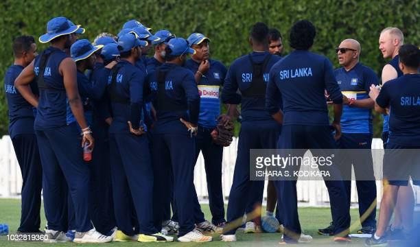 Sri Lankan coach Chandika Hathurusingha talks with team members during a training session at the Dubai Sports City in Dubai on September 13 2018 The...