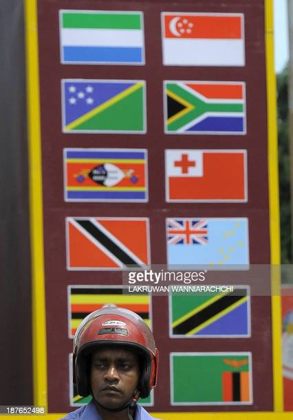 A Sri Lankan commuter rides his bicycle past an archway seen adorned with flags of Commonwealth nations in the capital Colombo on November 11 ahead...