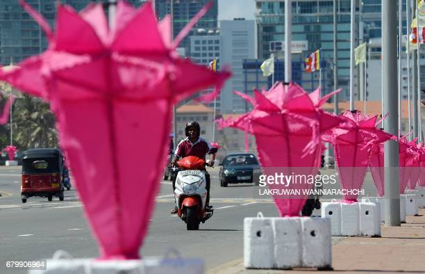 Sri Lankan commuters drive past decorative lanterns on the eve of the Vesak Festival in Colombo on May 7 2017 Sri Lankan Buddhists are preparing to...