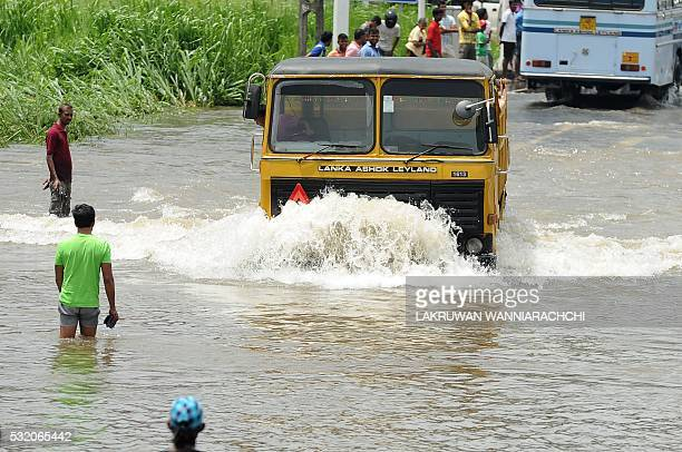 Sri Lankan commuters drive through floodwaters along an expressway in the suburb of Athurugeriya in capital Colombo on May 18 2016 Rescue workers in...