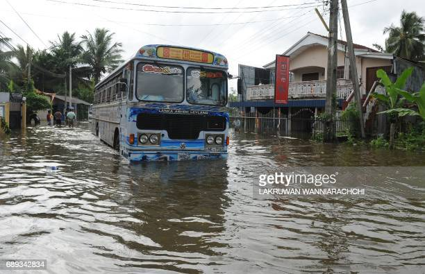 Sri Lankan commuters drive through floodwaters in Dodangoda village in Kalutara on May 28 2017 Emergency teams rushed to distribute aid on May 28 to...