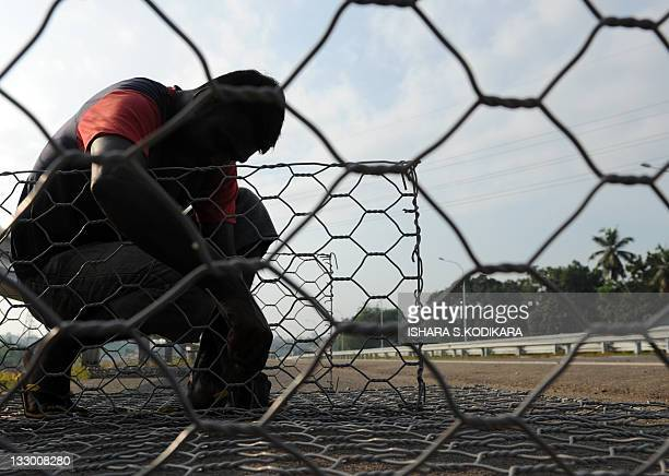Sri Lankan construction labourer works on the partially built Southern Highway Express lane in Kottawa on November 16, 2011. Sri Lanka is set to open...