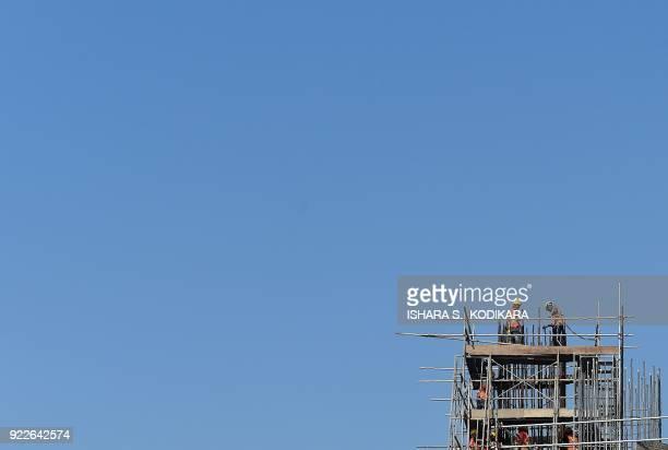 Sri Lankan construction labourers work on a new apartment building in Colombo on February 22 2018 / AFP PHOTO / ISHARA S KODIKARA
