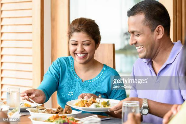 sri lankan couple during dinner, man holding plate - sri lankan culture stock pictures, royalty-free photos & images