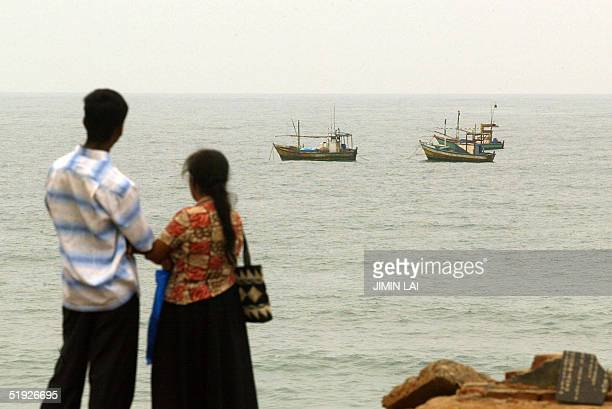 Sri Lankan couple look out to sea while fishing boats are anchored off the shore of the southern coastal town of Hambantota 08 January 2005 According...
