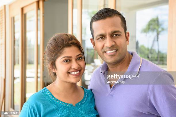 sri lankan couple outside house smiling towards camera - sri lankan culture stock pictures, royalty-free photos & images