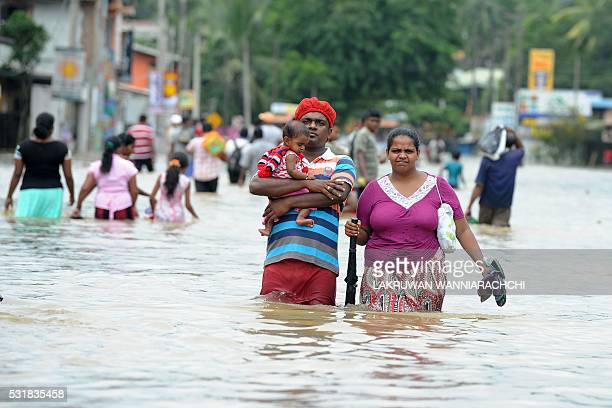 Sri Lankan couple with their child make their way through floodwaters in the suburb of Kaduwela in capital Colombo on May 17 2016 Emergency workers...