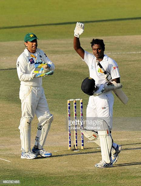 Sri Lankan cricket captain Angelo Mathews celebrates his century as Pakistan wicketkeeper Younis Khan looks on during the fourth day of the first...