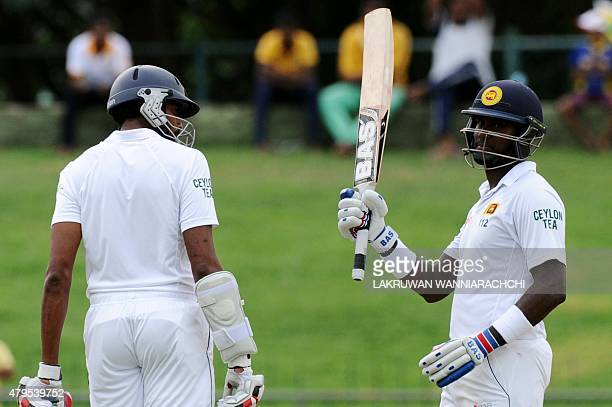 Sri Lankan cricket captain Angelo Mathews is watched by his teammate Jehan Mubarak as he raises his bat to the crowd after scoring a halfcentury...