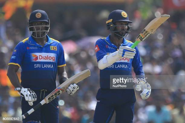 Sri Lankan cricket captain Angelo Mathews looks on as Upul Tharanga raises his bat after scoring 50 runs during the 2nd One Day International cricket...