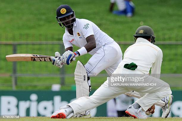 Sri Lankan cricket captain Angelo Mathews plays a shot as Pakistan cricketer Azhar Ali reacts during the third day of the third and final Test...