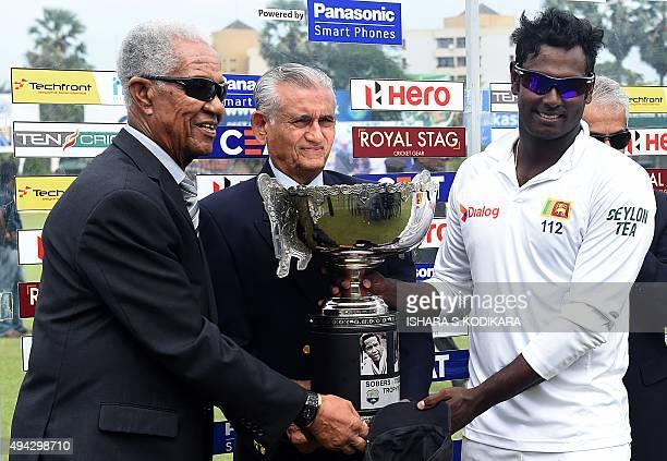 Sri Lankan cricket captain Angelo Mathews West Indian cricket legend Garfield Sobers and former Sri Lanka cricket captain Michael Tissera hold up the...