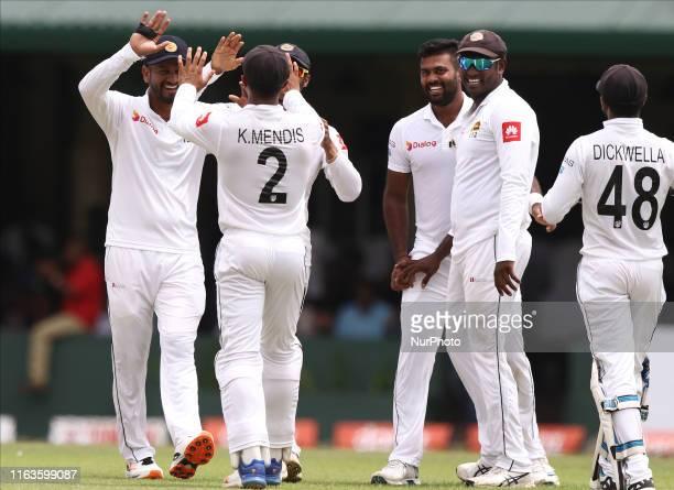 Sri Lankan cricket captain Dimuth Karunaratne celebrates with Kusal Mendis watched by Lahiru Kumara Angelo Mathews and Niroshan Dickwella after...