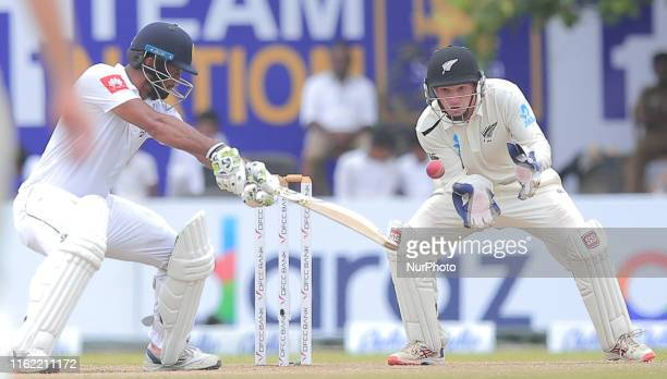 Sri Lankan cricket captain Dimuth Karunaratne plays a shot as New Zealand wicket keeper BJ Watling looks on during the fourth day's play of the first...