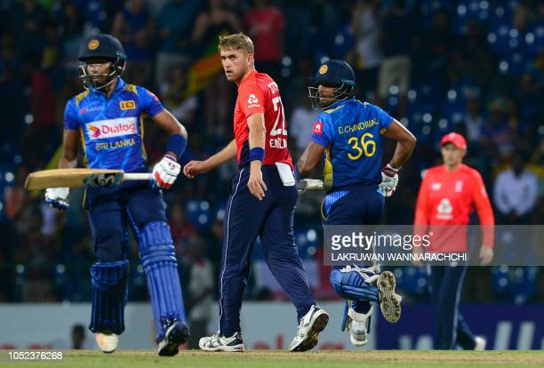 Sri Lankan cricket captain Dinesh Chandima and teammate Sadeera Samarawickrama run between the wickets as England cricketer Olly Stone looks on...