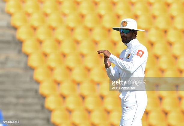Sri Lankan cricket captain Dinesh Chandimal signals for a third umpire review for an unsuccesful wicket of Indian cricketer Ajinkya Rahane during the...