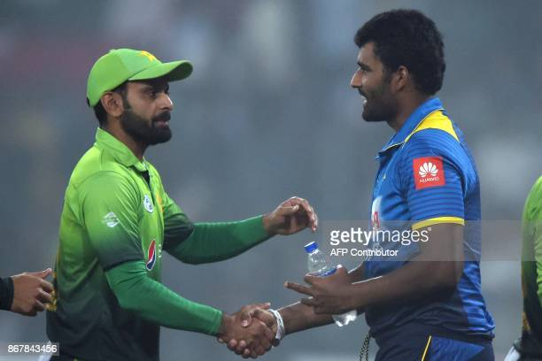 Sri Lankan cricket captain Thisara Perera shakes hands with Pakistani cricketer Mohammad Hafeez after the victory of Pakistan during the third and...