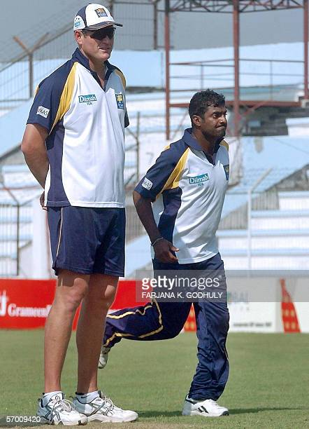 Sri Lankan cricket coach Tom Moody looks on as cricketer Muttiah Muralitharan runs to deliver a ball during a practice session at the Shahid Chadu...