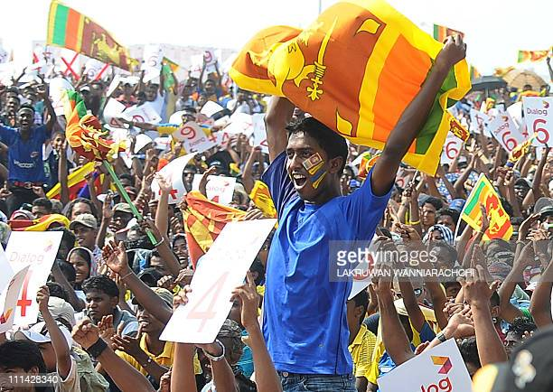 A Sri Lankan cricket fan holds up the national flag as they watch on a giant screen the Cricket World Cup final match between Sri Lanka and India in...
