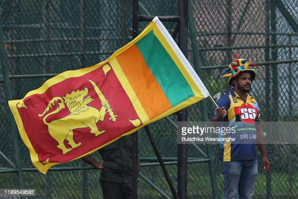 Sri Lankan cricket fan waves national flag as cheering during day one of the Second Test match between Sri Lanka and New Zealand at P Sara Oval...