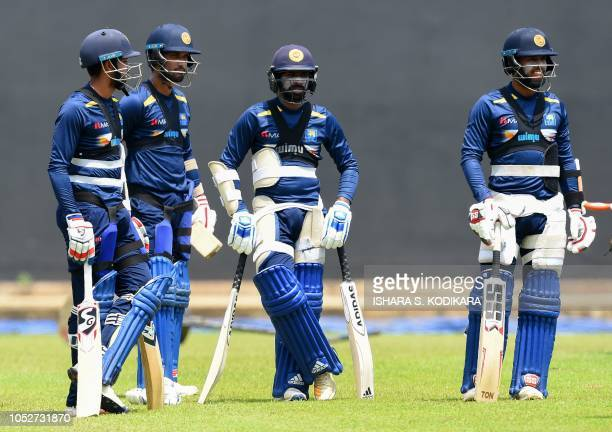 TOPSHOT Sri Lankan cricket team captain Dinesh Chandima Kusal Mendis Sadeera Samarawickrama and Niroshan Dickwella watch players during a practice...