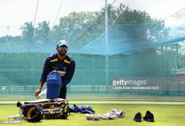 Sri Lankan cricket team captain Dinesh Chandimal puts on his leg pads during a practice session at the Rangiri Dambulla International Cricket Stadium...