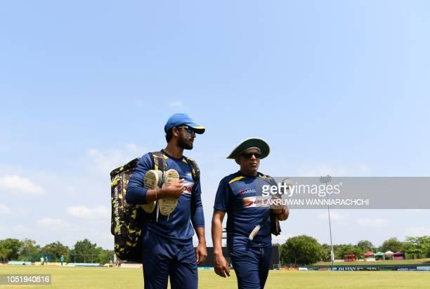 Sri Lankan cricket team captain Dinesh Chandimal speaks with coach Chandika Hathurusingha during a practice session at the Rangiri Dambulla...