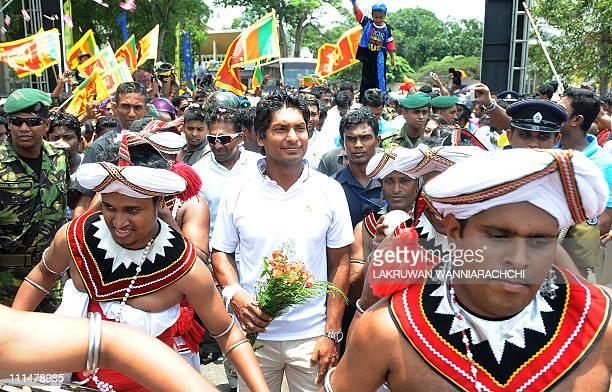 Sri Lankan cricket team captain Kumar Sangakkara with his teammates walks between traditional Sri Lankan Kandyan dancers performing at the team's...