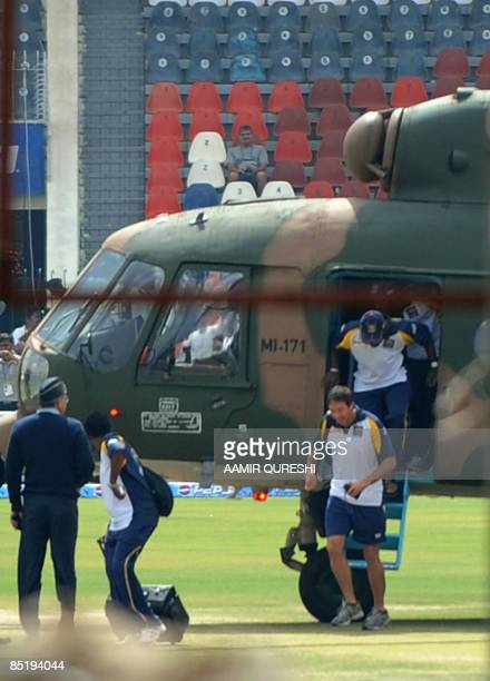 Sri Lankan cricket team members disembark from a Pakistani military helicopter onto the playing surface at The Gaddafi Stadium in Lahore on March 3,...