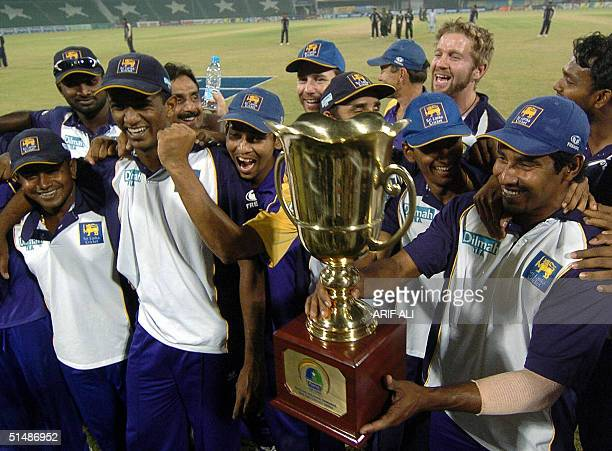 Sri Lankan cricket team players celebrate with the winners trophy of triseries tournament at the Gaddafi stadium in Lahore16 October 2004 Left armer...