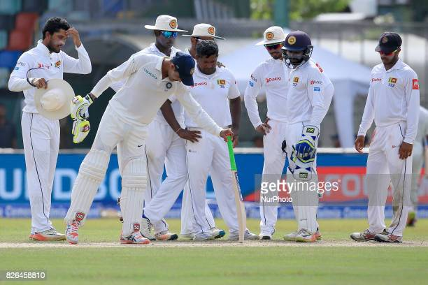 Sri Lankan cricket team players inspect a spot in the pitch that misbehaved with uneven bounce as Indian cricketer Ravindra Jadeja joins in during...