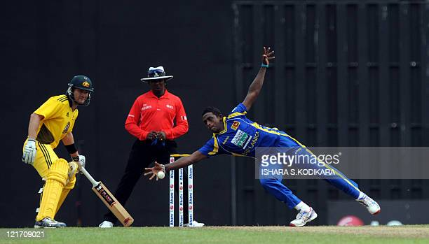 Sri Lankan cricketer Ajantha Mendis dives as he attempts to field a ball hit by unseen Australian cricketer Michael Clarke, as Shane Watson reacts...