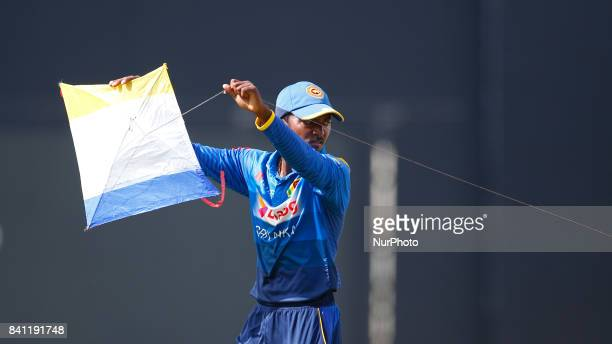 Sri Lankan cricketer Akila Dananjaya carries away a kite which landed in the playing area during the 4th One Day International cricket match between...