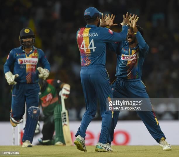 Sri Lankan cricketer Akila Dananjaya celebrates with teammate Upul Tharanga after dismissing Bangladesh's Liton Das during the sixth Twenty20...