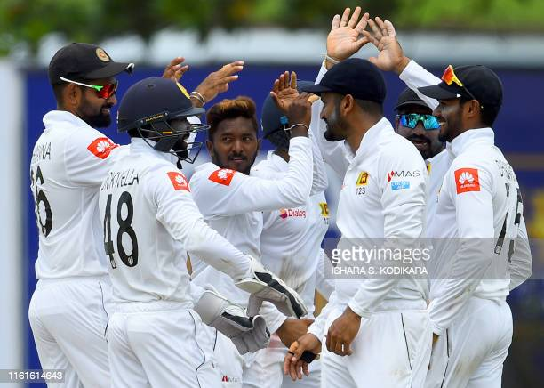 Sri Lankan cricketer Akila Dananjaya celebrates with teammates after dismissing New Zealand cricketer Jeet Raval during the first day of the opening...