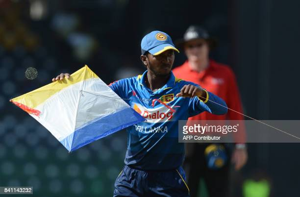 Sri Lankan cricketer Akila Dananjaya removes a kite that landed on the ground during the fourth one day international cricket match between Sri Lanka...