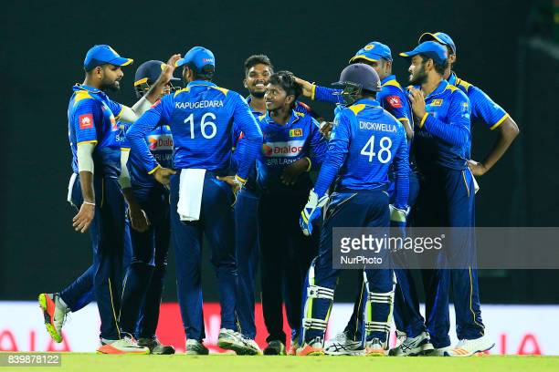 Sri Lankan cricketer and spinning bowler Akila Dananjaya celebrates with team mates after taking the wicket of India's Lokesh Rahul during the 3rd...