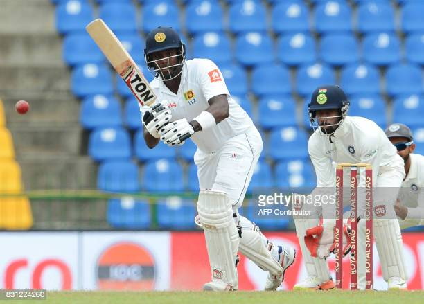 Sri Lankan cricketer Angelo Mathews is watched by Indian wicketkeeper Wriddhiman Saha as he plays a shot during the third day of the third and final...