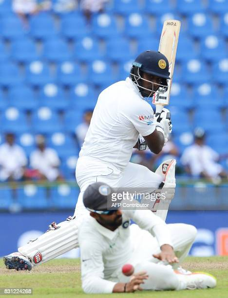 Sri Lankan cricketer Angelo Mathews plays a shot as Indian cricketer Ajinkya Rahane dives as he attempts to field a ball during the third day of the...